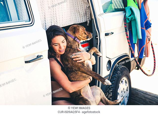 Woman sitting in camper van hugging pet dog