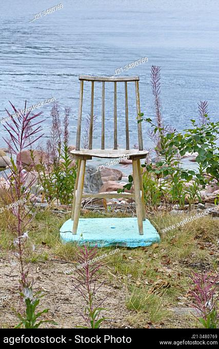 A wooden chair is standing on a piece of turquoise styrofoam on a grassy beach, facing away from the sea. Baltic Sea, Västernorrland, Sweden, Europe