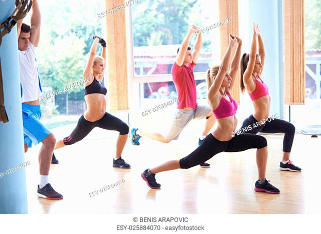 Group of people exercising at the gym and stretching