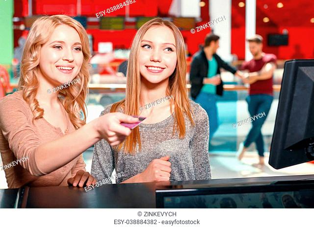 Make decision. Two young smiling women choosing type of entertainment, one of them is holding card