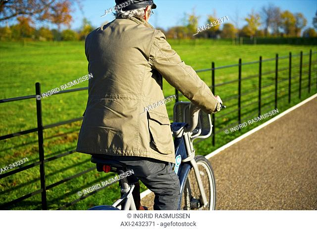 A man rides his bicycle on a gravel path in Hyde Park; London, England