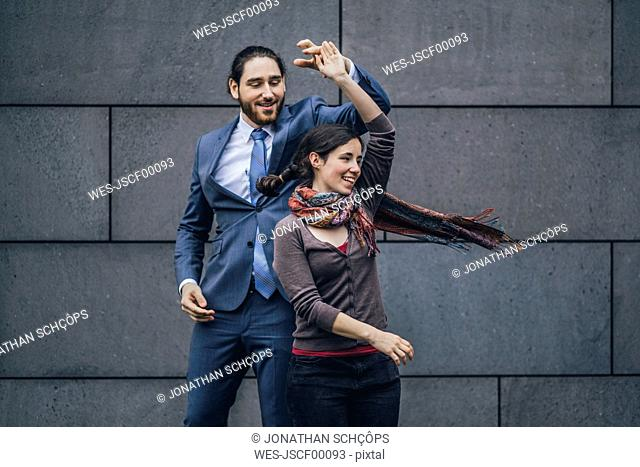 Happy businessman and woman dancing outdoors