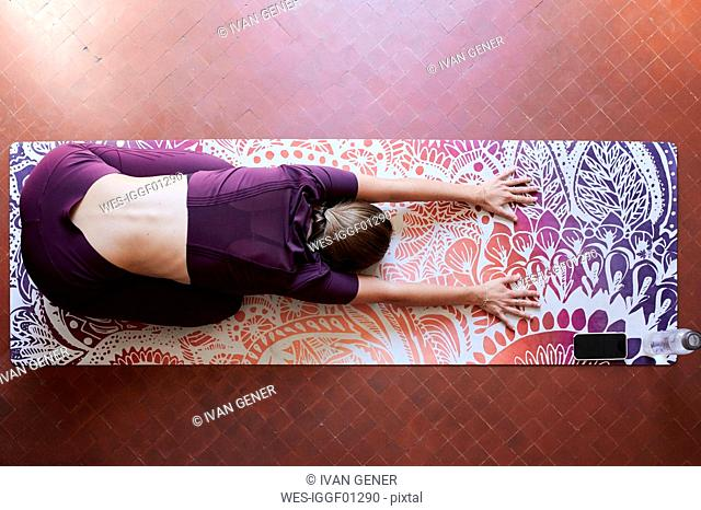 Young brunette woman practising yoga in student dorm, child position from above