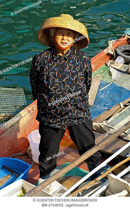 Old Chinese fishmonger with straw hat on her boat, Sai Kung, Hong Kong, China