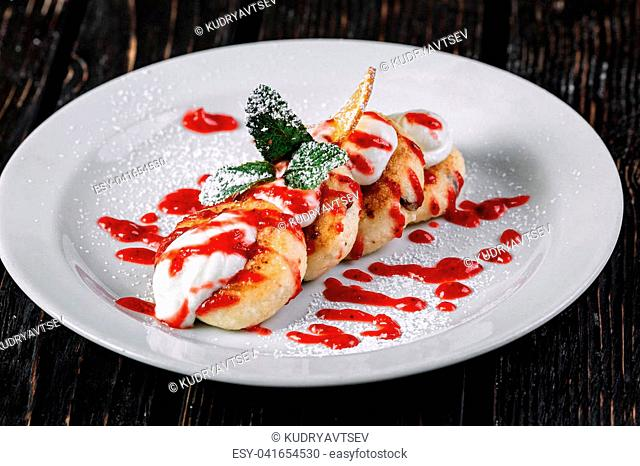 ?ottage pancakes with sour cream and jam on white plate on dark wood background