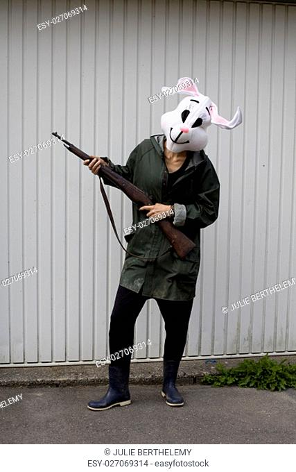 .woman wearing a rabbit mask hunting with shotgun in a forest