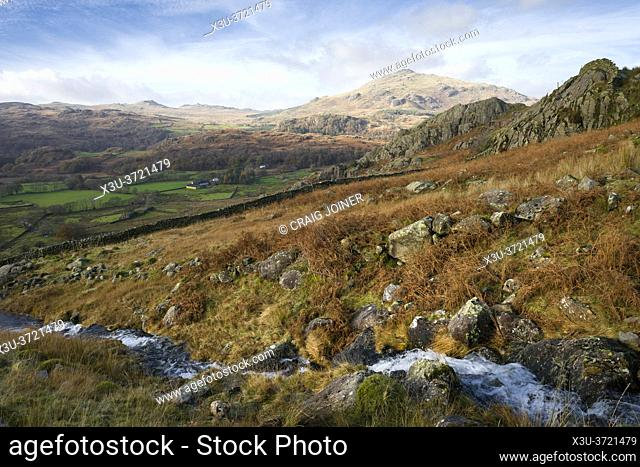 A stream flowing down from the Seathwaite Fells beside Tongue House High Close with the Duddon Valley and Harter Fell beyond in the Lake District National Park