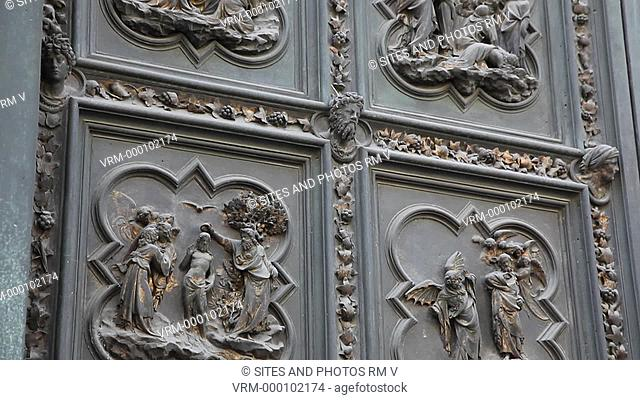 Exterior, CU, TILT up, daylight, view of the Baptistery north doors. Seen are gilded bronze relief scenes, made by Lorenzo Ghiberti between 1404-1424