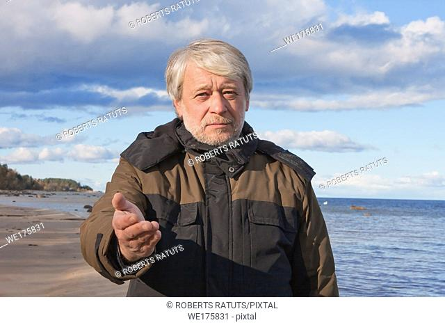 Mature poor man with grey hair at the Baltic sea asks for help in autumn day