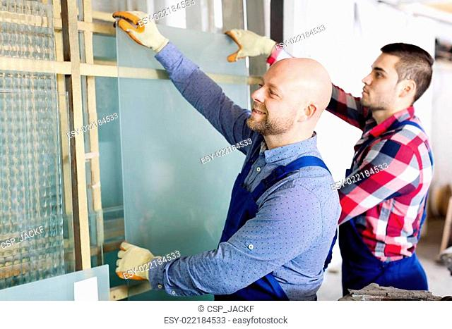 Two workers working with glass