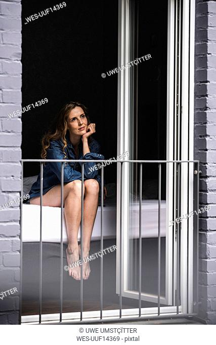 Thoughtful woman in denim shirt at home sitting on bed looking out of window