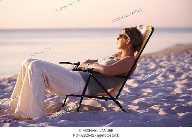 A woman sitting on a chair at the beach, watching the sunset