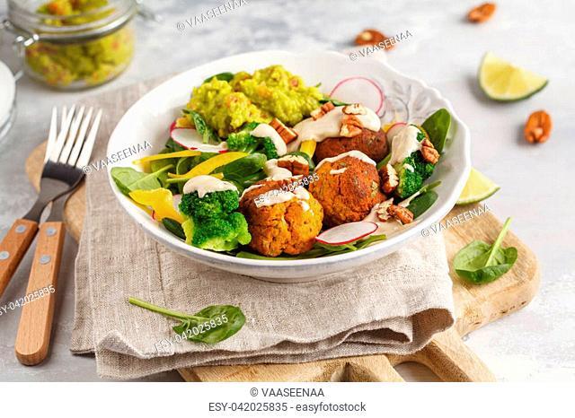 Vegan baked sweet potato meatballs, guacamole and vegetables salad. Light background, healthy vegetarian food concept