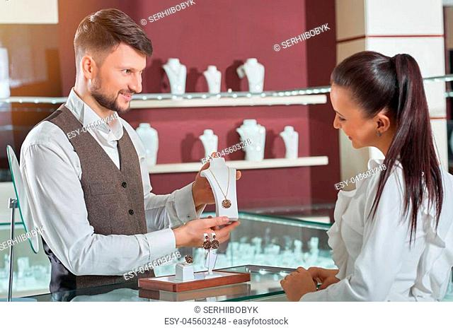 Elegance to wear. Professional jeweler smiling showing a necklace to his female customer working at his store business seller salesperson professionalism...