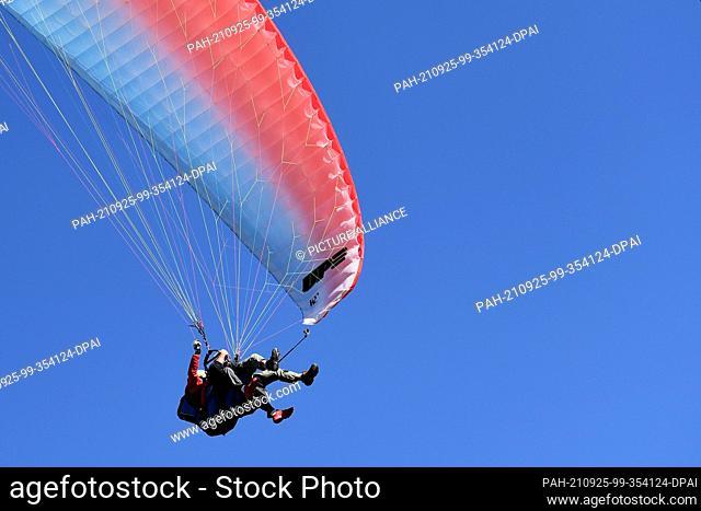 25 September 2021, Bavaria, Garmisch-Partenkirchen: Paragliders take advantage of the beautiful autumn weather for a flight under cloudless skies