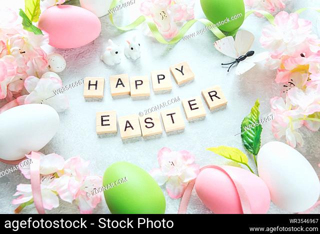 Beautiful delicate Easter composition with pink cherry flowers, multicolored Easter eggs, Easter bunny, butterfly and inscription