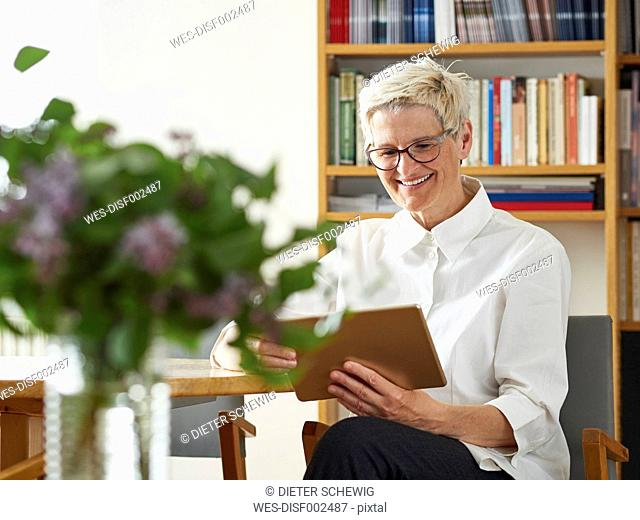 Portrait of smiling senior woman with digital tablet at home