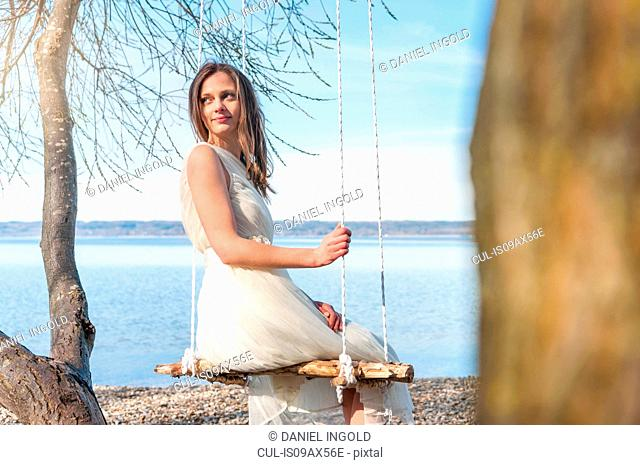 Rear view of woman on rope swing looking away over shoulder