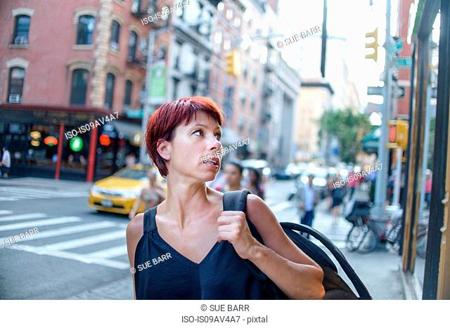 Mature woman looking over her shoulder on city street