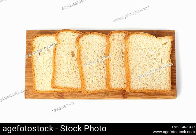 fresh bread made from white wheat flour is cut into slices on a wooden board, food is isolated on a white background, top view