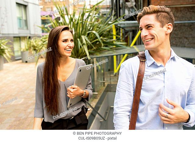 Young businesswoman and man walking and talking, London, UK