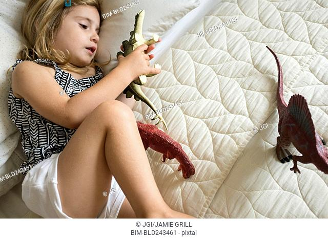 Caucasian girl laying on bed playing with toy dinosaurs