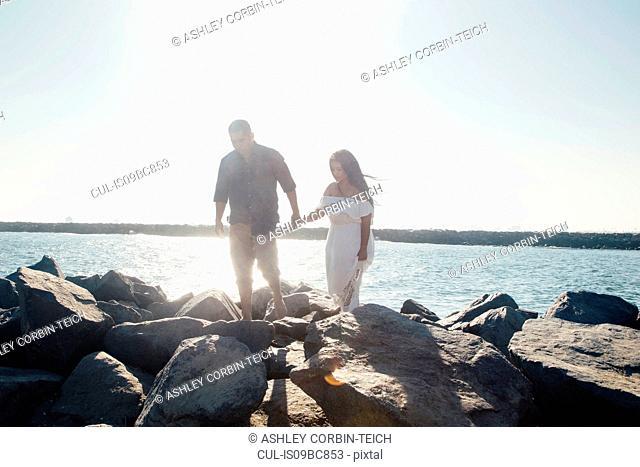 Couple walking on coastal rocks, holding hands, Seal Beach, California, USA