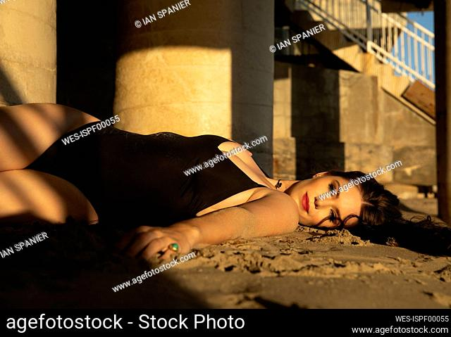 Smiling fashion model in one piece swimsuit lying on sand during sunset