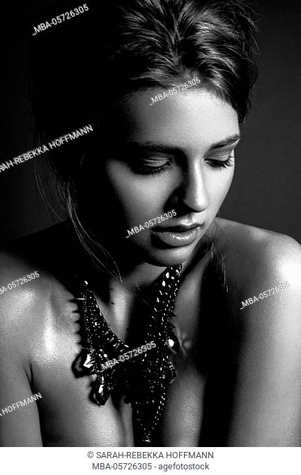 profile of a young woman, beauty portrait, black-and-white, eyes sensually closed, jewellery highlight in the neck, head sensually turned to the left