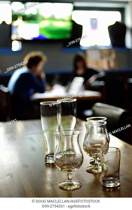 Empty beer glasses on a table in a craft brewery while a man and woman discuss something in the background