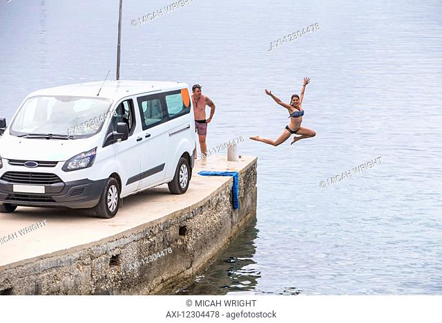 A couple stops for an early morning swim and shower after camping in their van; Croatia