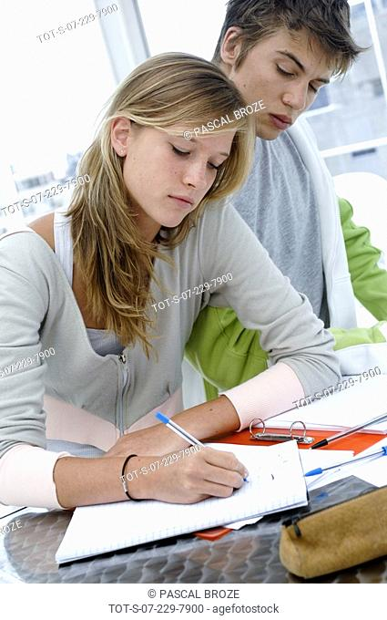 Close-up of a young woman writing on a textbook and a young man sitting beside her