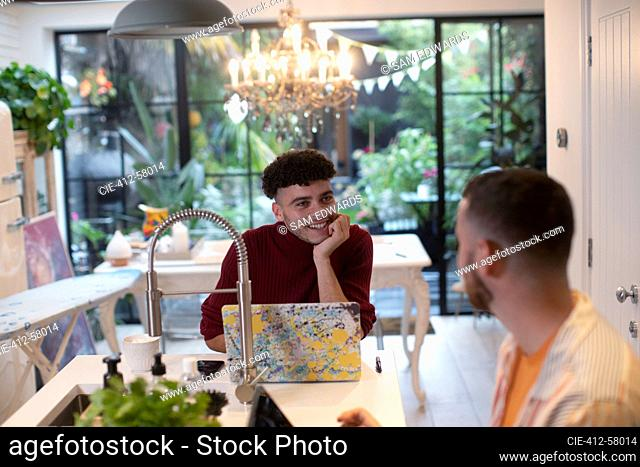 Gay male couple talking and using laptop in kitchen
