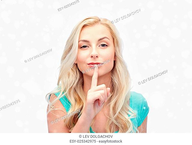 people, gesture, winter holidays, christmas and secret concept - beautiful young woman holding finger at her lips over snow