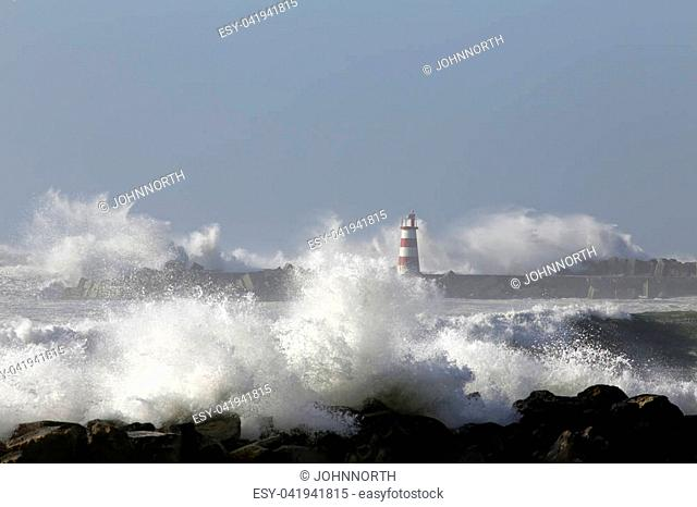 Beacon and pier of Povoa do Varzim e Vila do Conde fishing harbor and marina under heavy storm with strong wind and big waves, north of Portugal