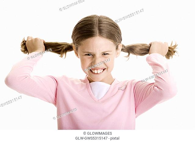 Portrait of a girl holding her pigtails