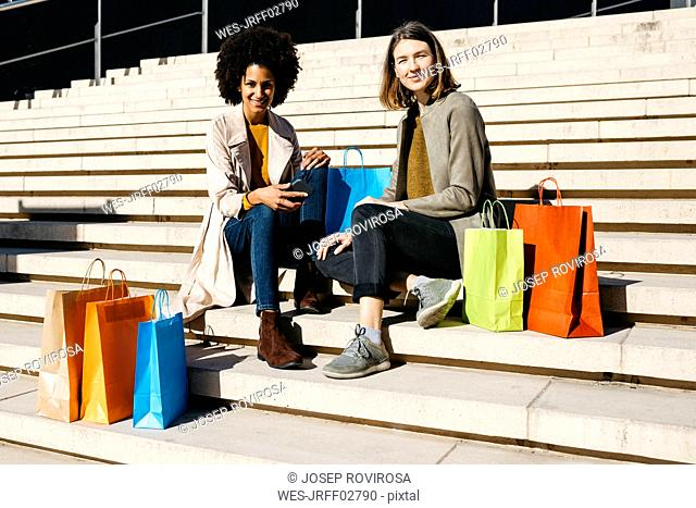 Portrait of two happy women with shopping bags sitting on stairs