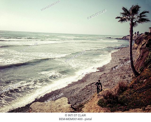Surfer walking on rocky beach, San Diego, California, United States
