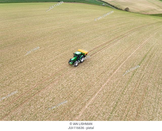 Aerial View Of Tractor Fertilizing Crop In Field