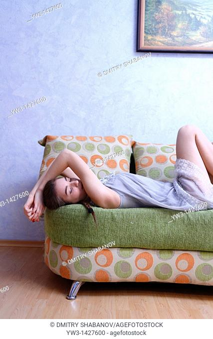 Portrait of a young blond woman lying on sofa
