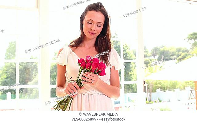 Pretty woman smelling bouquet of roses