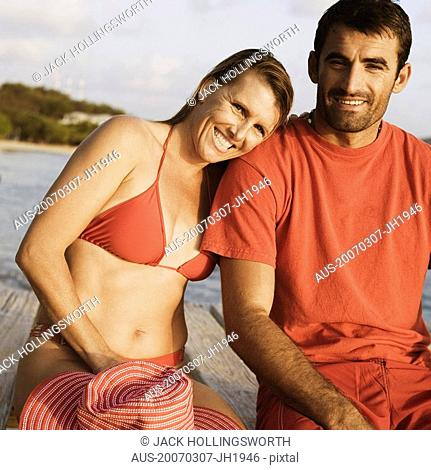 Portrait of a mid adult couple sitting on a pier and smiling
