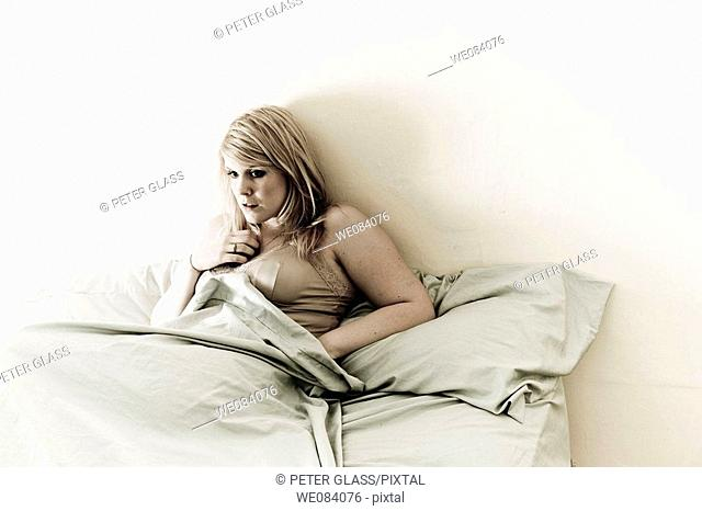Young blond woman sitting on her bed