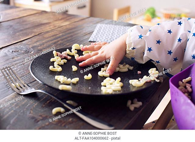 Child eating macaroni with her hand, cropped