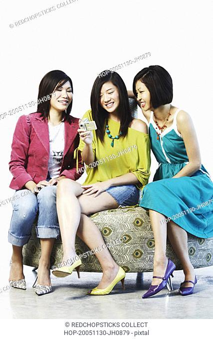 Three young women using a digital camera