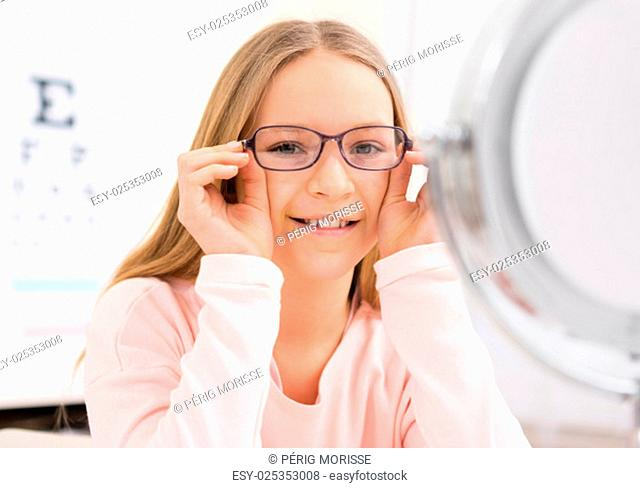 VIew of a Young little girl trying glasses at the optician