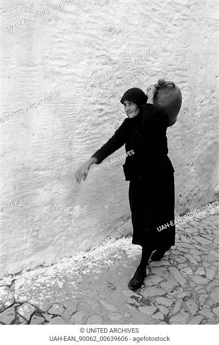 Travel to Greece - Greece - old woman from Mykonos island, Cyclades. Image date circa 1954. Alte Frau trägt einen Krug auf der Insel Mykonos, Griechenland 1954