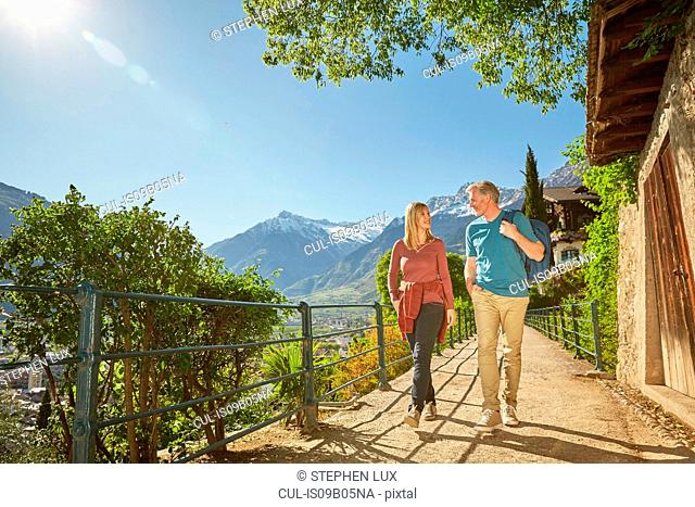 Mature couple hiking along country road, Meran, South Tyrol, Italy