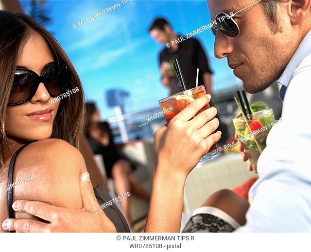 Couple having cocktail outdoors