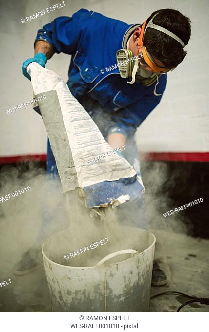 Bricklayer pouring cement powder in bucket